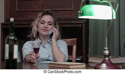 Attractive young woman enjoying a glass of wine sitting at her desk while talking on the phone after a long work day