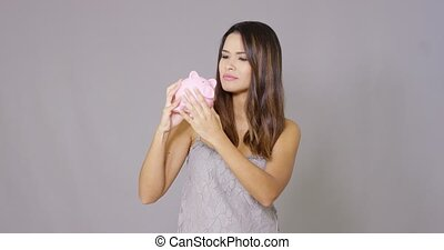 Attractive young woman examining her piggy bank