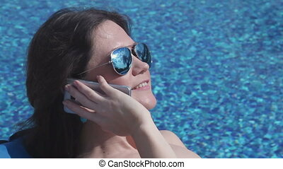 """""""Attractive young woman flirting, talking on phone, suntanning"""""""