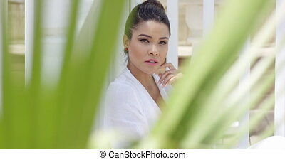 Attractive young woman framed by palm leaves