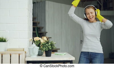 Attractive young woman funny housekeeper is having fun during housecleaning, young lady is singing and dancing listening to music in headphones and dusting table.