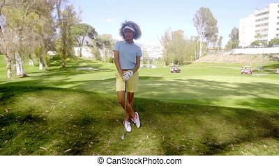 Attractive young woman golfer standing watching leaning on...
