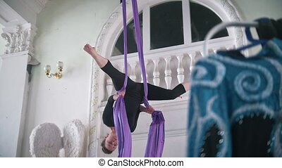 Attractive young woman gymnast performing on aerial silk -...