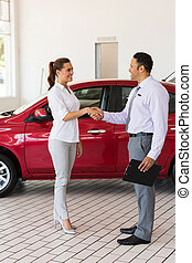 young woman handshaking with car salesman