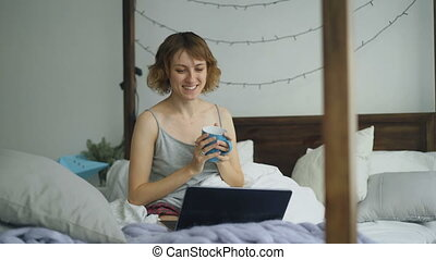 Attractive young woman having online video chat with friends using laptop camera while sitting on bed at home