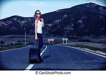 hitchhiking - Attractive young woman hitchhiking along a ...