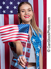 Attractive young woman holding american flag in hand and smiling at camera, woman celebrating Independence Day of America