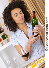 attractive young woman holding bottle of red wine