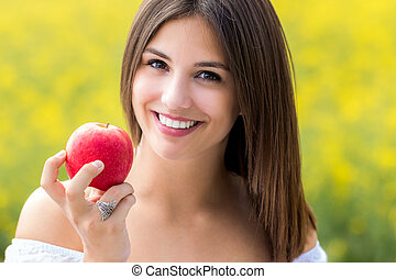 Attractive young woman holding red apple outdoors.