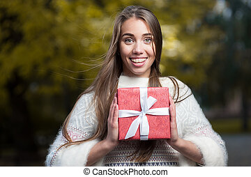 attractive young woman holding red present