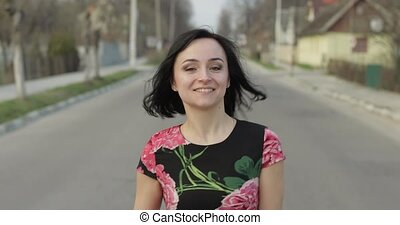 Attractive young woman in a dress with flowers moving to camera and smiles