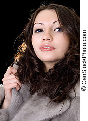 Attractive young woman in a fur coat