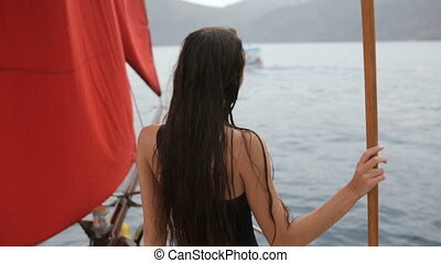 Attractive young woman in a swimsuit posing on the yacht in slow motion