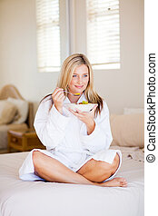 attractive young woman in bathrobe eating fruit salad on bed