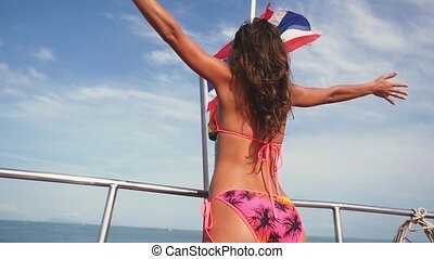 Attractive young woman in bikini is standing with arms outstretched on the upper deck of the ship. slow motion. 1920x1080