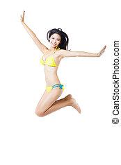 Attractive young woman in bikini jumping
