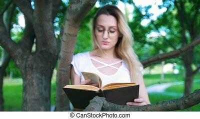 Attractive young woman in eyeglasses reading a book leaning on a tree branch