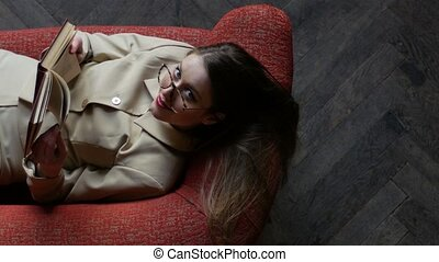 Attractive young woman in glasses in beige suit sitting on the red sofa while reading books and playfully beckoning hand. Top view