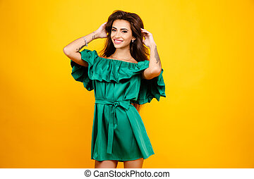 Attractive young woman in green dress on yellow background. Studio shot.