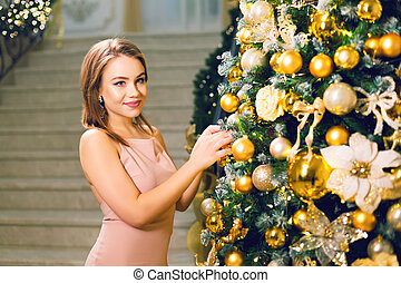 Attractive young woman in pink dress dressing up a Christmas