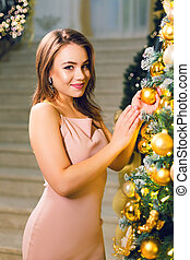 Attractive young woman in pink dress holding Christmas ball in her hand.
