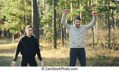 Attractive young woman in sportswear is exercising in park with her boyfriend doing warm-up rotating arms talking and smiling. Healthy lifestyle and nature concept.
