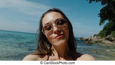 Attractive young woman in sunglasses near water