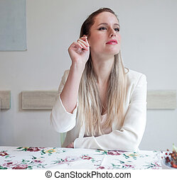 Attractive young woman in the restaurant calling waiter