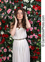 Attractive young woman in white dress on flower wall