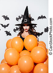 Attractive young woman in witch halloween costume with orange balloons