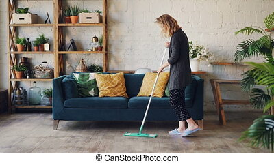 Attractive young woman is cleaning living room mopping the floor doing housework. Beautiful loft style apartment with modern furniture and plants is visible.