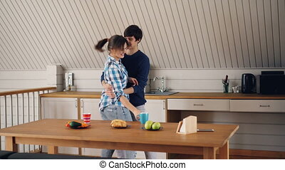 Attractive young woman is having fun with her handsome Asian boyfriend at home dancing, kissing and eating pastry. Girl and guy are wearing casual clothing.
