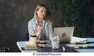 Attractive young woman is talking on skype on laptop while sitting at table in modern office. She is speaking emotionally, gesturing and laughing.