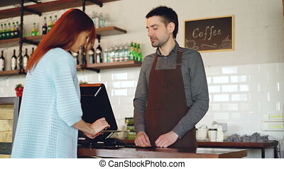Attractive young woman is talking to friendly male cashier,...