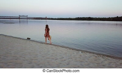 attractive young woman is walking on a sand of the river bank