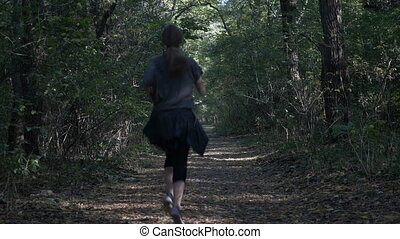 Attractive young woman jogging in nature through a shady...