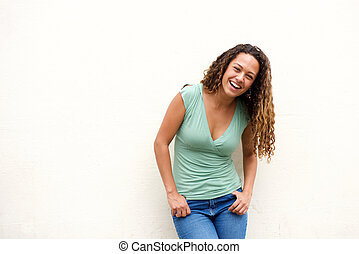 Attractive young woman laughing against white background