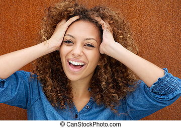 Attractive young woman laughing with hands in hair