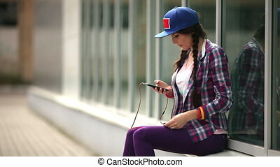 Attractive young woman listening music on smartphone in the city