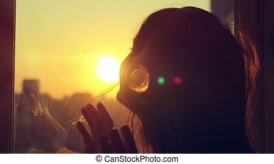 Attractive young woman listening to music in headphones at city blurred background. Enjoying the tunes in slowmotion. Taking picture with her smartphone at sunset