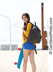 Attractive young woman looking over shoulder with skateboard
