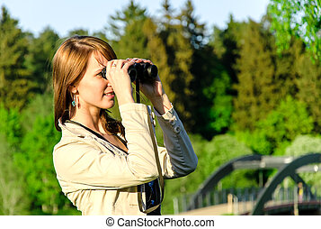Attractive young woman looking through binoculars