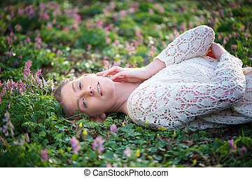 Attractive young woman lying on grass and flowers