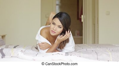 Attractive young woman lying on her bed