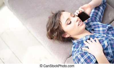 Attractive young woman lying on the sofa and talking on the phone. Young woman talking on the cell phone and smiling. Close up.