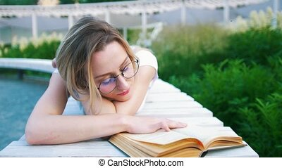 Attractive young woman lying reading a book in urban garden