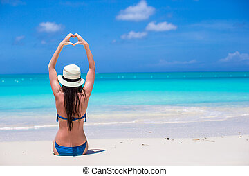 Attractive young woman making a heart with hands on the beach