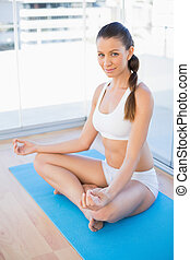 Attractive young woman meditating in lotus position in...
