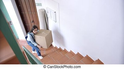 Attractive young woman moving house carrying a cardboard...