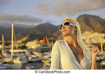 Attractive young woman near the yachts